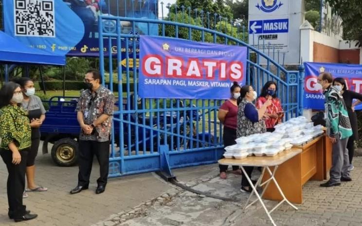 Jajaran pimpinan dan staf Universitas Kristen Indonesia menyediakan paket sarapan dan vitamin gratis untuk warga yang melintas depan kampus UKI, Jakarta, Kamis (18/3/2021).  - ANTARA