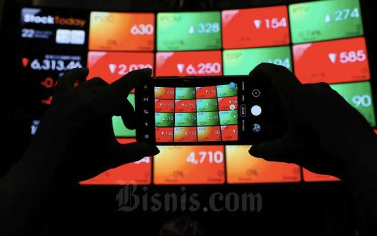 Pengunjung memotret papan elektronik yang menampilkan pergerakan indeks harga saham gabungan (IHSG) di Bursa Efek Indonesia, Jakarta, Senin (22/3/2021). Bisnis - Eusebio Chrysnamurti