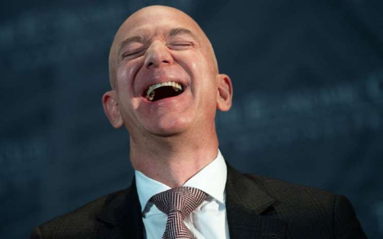 Jeff Bezos, CEO Amazon, sedang tertawa. Menghentikan pikiran negatif mengindarkan risiko stres.  - Bloomberg