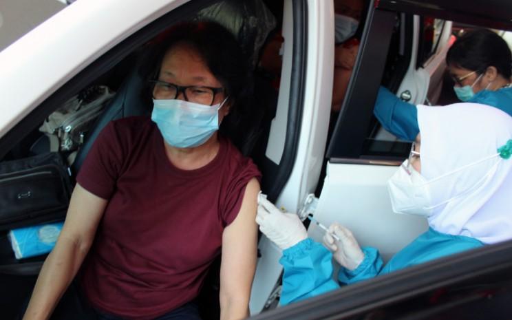 Petugas kesehatan menyuntikkan vaksin Covid-19 untuk warga lanjut usia (lansia) secara drive thru di halaman GOR Pajajaran, Kota Bogor, Jawa Barat, Rabu (17/3/2021).  - ANTARA
