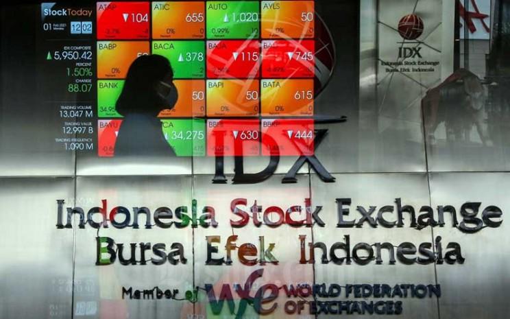 Pekerja melintasi papan elektronik yang menampilkan pergerakan Indeks Harga Saham Gabungan (IHSG) di Bursa Efek Indonesia, Jakarta, Senin (1/2/2021). Bisnis - Eusebio Chrysnamurti