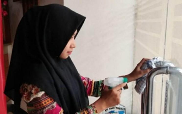 Seorang karyawan hotel di Tanjung Balai Karimun, Kabupaten Karimun, Kepulauan Riau, membersihkan gagang pintu masuk hotel untuk pencegahan penyebaran wabah Covid-19. - Antara/Dokumentasi Pribadi