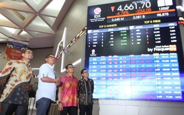 Direktur PT Bursa Efek Indonesia Inarno Djajadi (kedua kiri), didampingi Direktur Hasan Fawzi (dari kiri), Direktur Laksono W. Widodo, dan Direktur I Gede Nyoman Yetna memantau langsung pergerakan perdagangan harga saham melalui layar monitor elektronik di  Jakarta, Juman (13/3/2020). Indeks Harga Saham Gabungan (IHSG) bergerak ke level 4.656,031 sesaat setelah perdagangan saham dibuka kembali .  Perdagangan saham sempat dihentikan sementara pada pukul 09.15 WIB. Bisnis - Dedi Gunawan