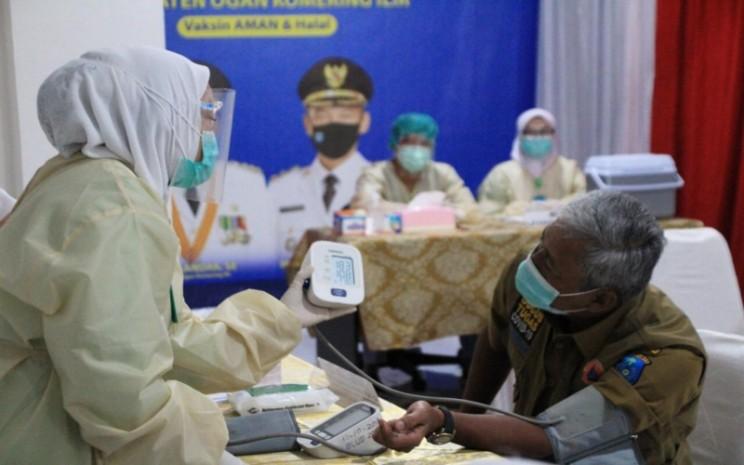 Petugas vaksinator menunjukkan tensi darah Bupati Kabupaten Ogan Komering Ilir Iskandar saat proses pemberian vaksin Covid/19. istimewa