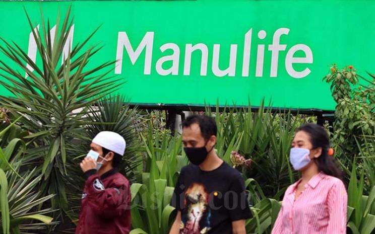 Warga melintas didekat logo perusahaan PT Asuransi Jiwa Manulife Indonesia di Jakarta, Senin (11/5/2020). Bisnis - Eusebio Chrysnamurti