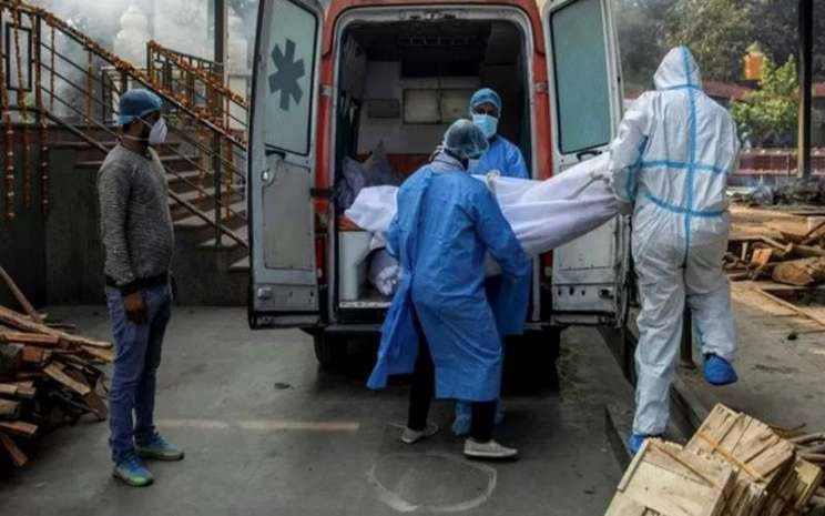 Tenaga kesehatan dan kerabat membawa jenazah seorang pria, yang meninggal dunia akibat penyakit  Covid-19 dari ambulans ke krematorium di New Delhi, India, Jumat (13/11/2020). - Antara/Reuters\\r\\n