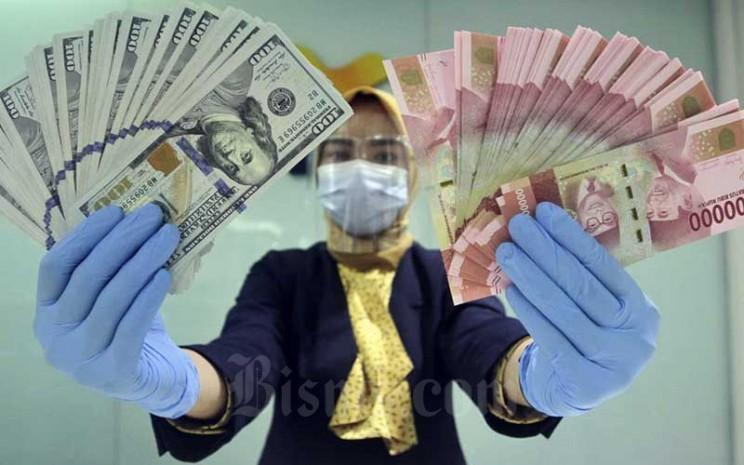 Karyawan merapikan uang dolar dan rupiah di Kantor Cabang Bank Mandiri di Jakarta, Kamis (14/1/2021). Bisnis - Himawan L Nugraha