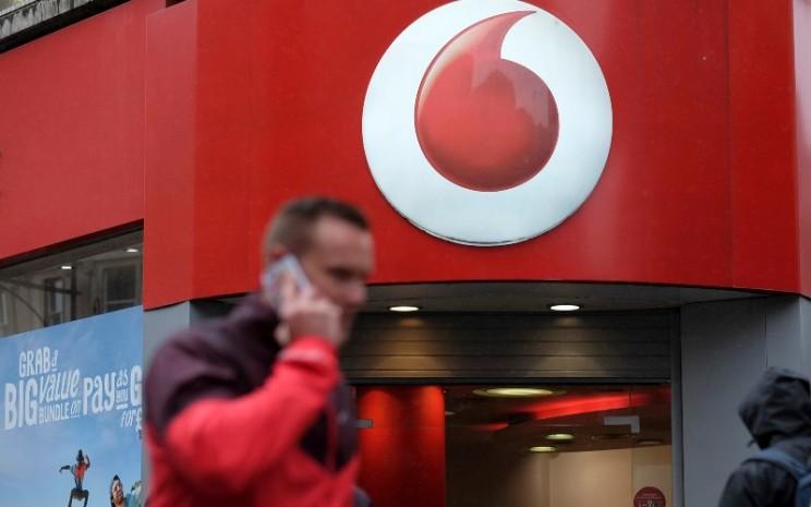 Seorang pria tengah mengangkat telepon di depan gerai Vodafone di London./Simon Dawson.  - Bloomberg