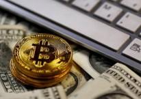 Ilustrasi Bitcoin diletakkan di atas lembaran uang dolar AS./REUTERS-Dado Ruvic