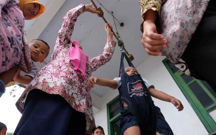 Petugas kader kesehatan desa menimbang balita di Posyandu Desa Danupayan, Bulu, Temanggung, Jawa Tengah, Rabu (11/3/2020).  - ANTARA FOTO/Anis Efizudin