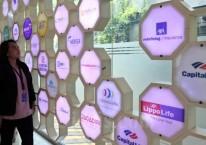 Karyawan melihat logo-logo perusahaan asuransi yang berada di Kantor Asosiasi Asuransi Jiwa Indonesia (AAJI) di Jakarta, Senin (2/3/2020). Bisnis/Eusebio Chrysnamurti