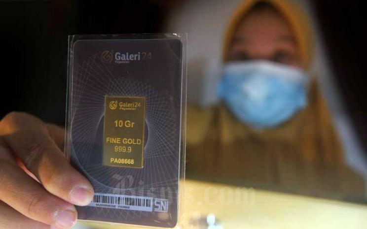 Karyawati menunjukkan emas batang di Galeri 24 Pegadaian di Jakarta, Senin (1/2/2021). Bisnis - Abdurachman