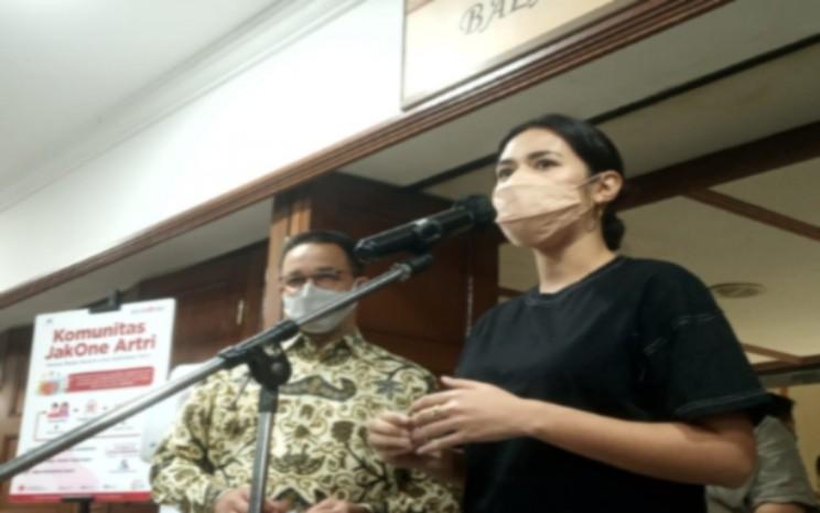 Penyanyi Raisa Andriana mendampingi Gubernur DKI Jakarta Anies Baswedan saat menyampaikan keterangan pers seusai vaksinasi 250 pekerja kreatif di Balai Kota DKI Jakarta, Kamis (22/4 - 2021). Nyoman Ary Wahyudi
