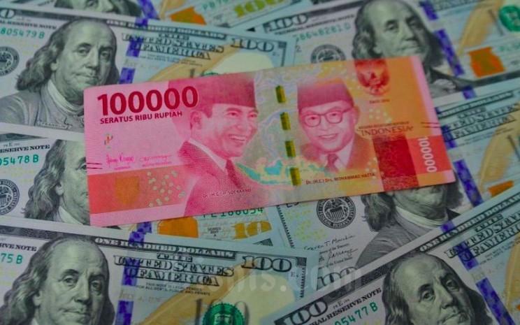 Petugas menunjukkan mata uang dolar AS dan rupiah di Money Changer, Jakarta, Senin (19/4/2021). Bisnis - Fanny Kusumawardhani