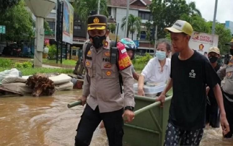 Kapolsek Kembangan Jakarta Barat Kompol Khoiri menarik gerobak yang dinaiki Aisyah (65) untuk menerjang banjir di Jalan Puri Kembangan, Jakarta Barat, Sabtu (20/2/2021).  - Antara