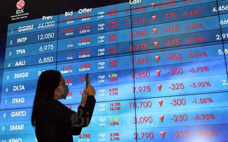 Pengunjung berada didekat papan elektronik yang menampilkan perdagangan harga saham di lantai Bursa Efek Indonesia di Jakarta, Jumat (13/3/2020). Bisnis - Dedi Gunawan
