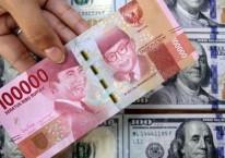 Petugas menunjukkan uang rupiah dan dolar AS di salah satu gerai penukaran mata uang asing di Jakarta, Senin (16/3/2020)./Bisnis-Arief Hermawan P