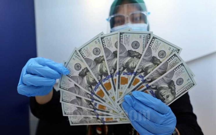 Karyawan menunjukan Dolar AS di Jakarta, Rabu (27/1/2021). Nilai tukar rupiah di pasar spot ditutup menguat 15 poin atau 0,11 persen menjadi Rp14.050 per dolar AS. Bisnis - Eusebio Chrysnamurti