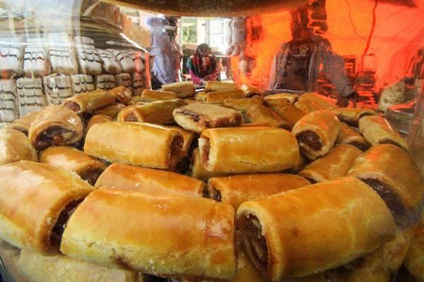 Penjual melayani pembeli kue kering khas lebaran di pusat Kota Lhokseumawe, Aceh, Rabu (6/6).  - Antara