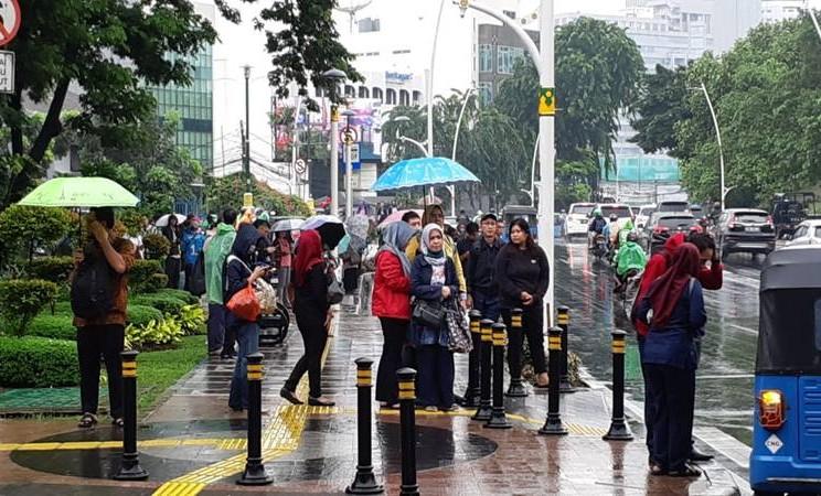Sejumlah karyawan menunggu angkutan umum di kawasan Sudirman Jakarta Pusat Selasa (25/2/2020). JIBI/Bisnis - Anya Dhyaksa