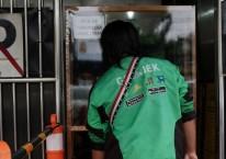 Pengemudi Gojek mengambil pesanan makanan di Jakarta, Indonesia, Selasa (5/1/2021)./Bloomberg-Dimas Ardian