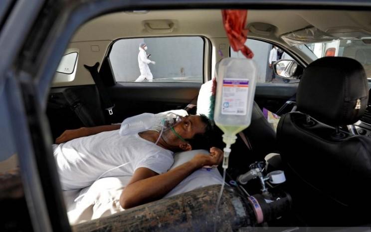 Seorang pasien dengan gangguan pernapasan berbaring di dalam mobil sambil menunggu untuk masuk rumah sakit Covid-19 untuk perawatan di tengah penyebaran penyakit virus corona di Ahmedabad, India, Kamis (22/4/2021).  - Antara/REUTERS