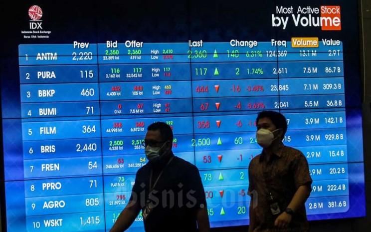 Pekerja melintasi papan elektronik yang menampilkan pergerakan Indeks Harga Saham Gabungan (IHSG) di Bursa Efek Indonesia, Jakarta, Senin (1/2/2021).  - Bisnis/Eusebio Chrysnamurti
