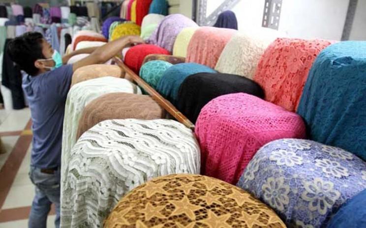 Pedagang menata kain tekstil. Bahan katun banyak dipakai untuk berbagai jenis pakaian.  - Bisnis/Arief Hermawan