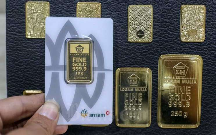 Karyawan menunjukan emas di salah satu Bank di Jakarta, Senin (8/3/2021). Bisnis - Eusebio Chrysnamurti