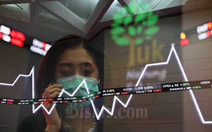 Pengunjung berada di dekat papan elektronik yang menampilkan pergerakan Indeks Harga Saham Gabungan (IHSG) di Bursa Efek Indonesia, Jakarta, Jumat (17/7/2020). Bisnis - Eusebio Chrysnamurti