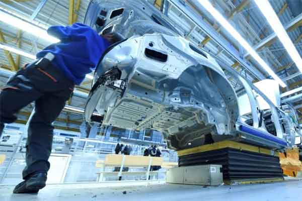 Seorang pekerja tengah merakit komponen kendaraan di pabrik mobil.  - Reuters