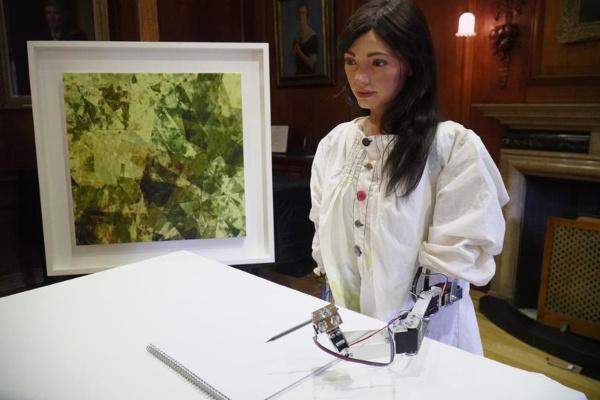 Ilustrasi - Seniman AI yang bernama bernama Ai-Da mengenakan blus putih dan rambutnya yang hitam terurai. Ai-Da terlihat seperti artis yang sedang bekerja saat dia mempelajari subjeknya dan meletakkan pensil di atas kertas. - Bisnis/Reuters