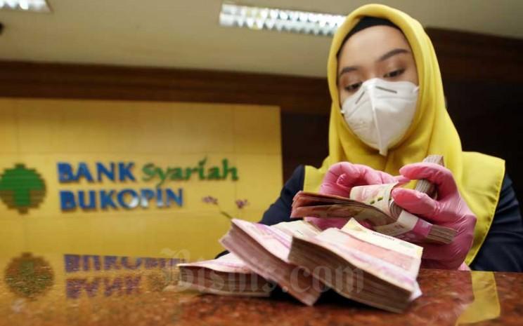 Karyawan menghitung mata uang rupiah di Bank Bukopin Syariah, Jakarta, Kamis (11/2/2021). Bisnis - Abdullah Azzam