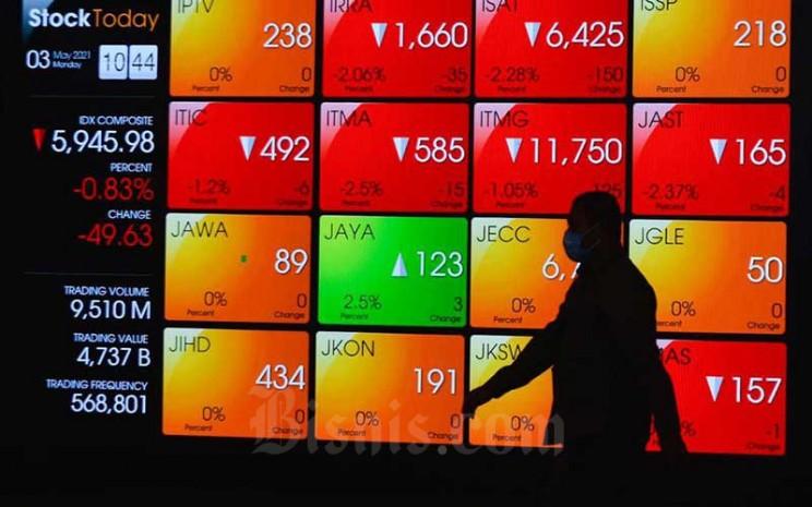 Karyawan melintas di depan papan elektronik yang menampilkan pergerakan Indeks Harga Saham Gabungan (IHSG) di Bursa Efek Indonesia, Jakarta, Senin (3/5/2021). Bisnis - Fanny Kusumawardhani