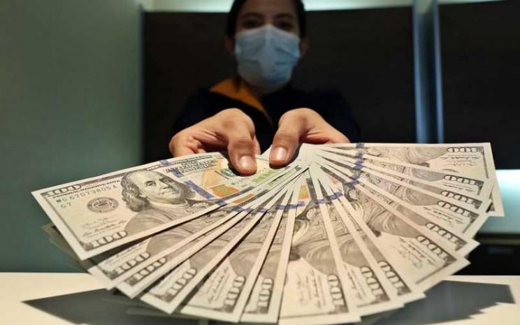 Karyawan menunjukan dolar AS di Jakarta, Rabu (11/11/2020).Bisnis - Eusebio Chrysnamurti