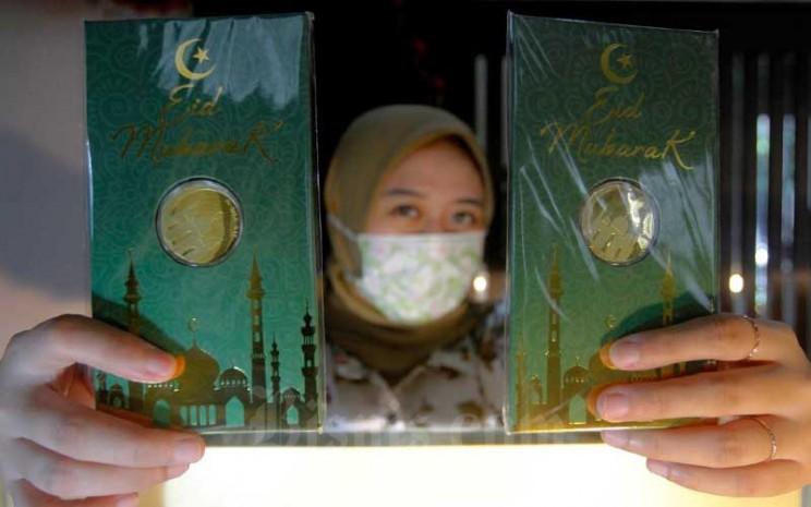 Karyawati menunjukan emas batangan edisi Idul Fitri di Kantor Pusat Pegadaian, Jakarta, Selasa (5/5/2020). Bisnis - Himawan L Nugraha