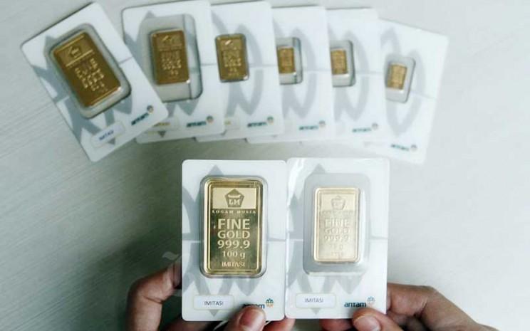 Karyawan menunjukan replika emas logam mulia di Butik Antam, Jakarta, Selasa (8/9/2020). Harga emas PT Aneka Tambang Tbk. pada hari perdagangan Selasa (8/9/2020) menurun dibandingkan dengan perdagangan hari sebelumnya. Bisnis - Himawan L Nugraha