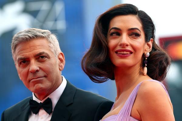 """Aktor yang juga sutradara George Clooney dan istrinya Amal berpose dalam acara 'red carpet' untuk film """"Suburbicon"""" di Festival Film Venesia ke-74 di Venesia, Italia. - Reuters"""