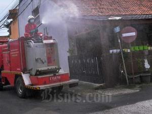 Petugas Pemadam Kebakaran Semprotkan Cairan Disinfektan di Lingkungan Perumahan
